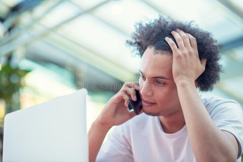 Zwyci?ski przystojny m??czyzna patrzeje jego laptop podczas gdy siedz?cy w jaskrawym ?ywym pokoju zdjęcie royalty free