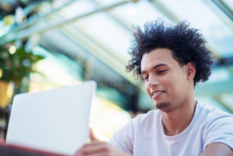 Zwyci?ski przystojny m??czyzna patrzeje jego laptop podczas gdy siedz?cy w jaskrawym ?ywym pokoju zdjęcie stock