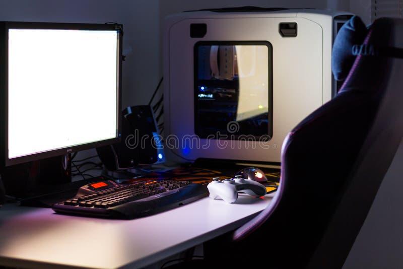 Zwyczaj - budujący komputer stacjonarny dla hazardu na stole z joystickiem, monitor, klawiatura, krzesło pod niskim światłem Sele zdjęcia royalty free
