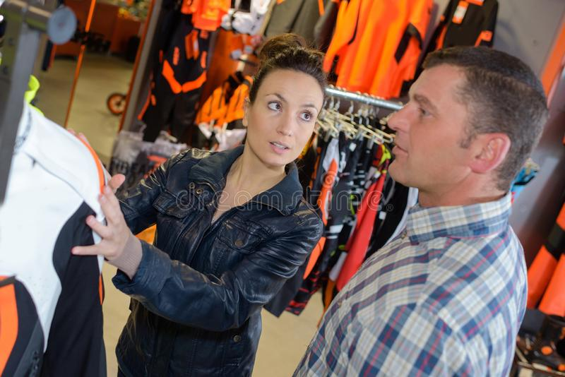 Zwyczajna para wybiera kurtkę przy sklepem odzieżowym zdjęcia royalty free