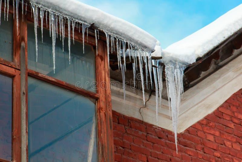 Zwyczajni sople wiesza od osaczają dach nad okno przeciw niebieskiemu niebu i biel chmurnieje zdjęcie royalty free