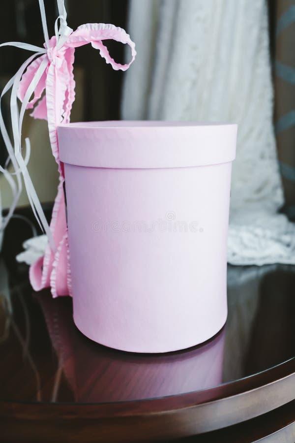 Zylindergeschenkbox mit Bändern auf dem Holztisch lizenzfreie stockfotos