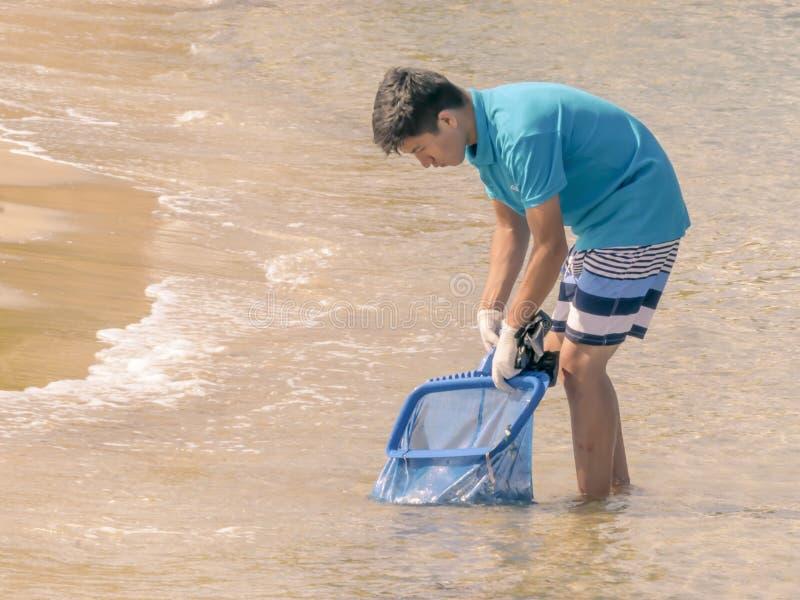 ZYPERN, KARAVAS, ALSANCAK - 10. JUNI 2019: Junger Arbeitnehmer, der die Küste vom Rückstand und vom Abfall säubert Mann, der mit  lizenzfreie stockbilder