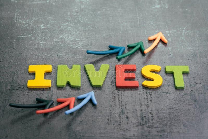 Zysk lub przyrost od inwestorskiego pojęcia wskazuje w górę mapy z kolorowymi listami jako, strzały buduje słowo INWESTUJEMY na l fotografia stock