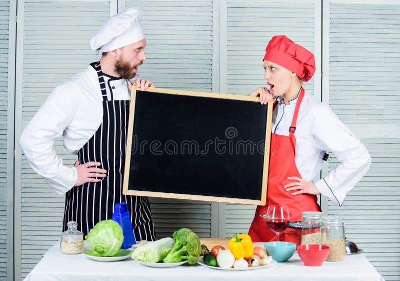 Zyskiwać pasmo umiejętności Para mężczyzny i kobiety mienia pusty blackboard w kucharstwo szkole Mistrzowski kucharz i przygotowy zdjęcie stock