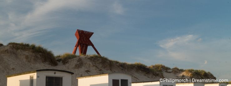 Seamark in sand dunes with beach cabins