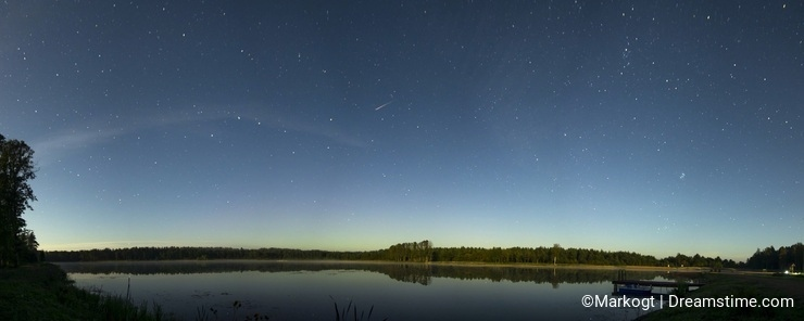 Beautiful night lake panorama with falling star.