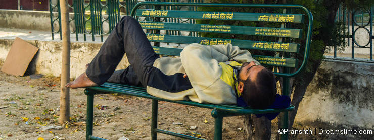 A poor person taking nap on bench
