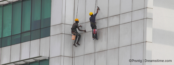 Workers cleaning or painting a multistory building