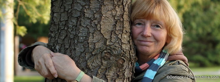 Mature woman embracing tree