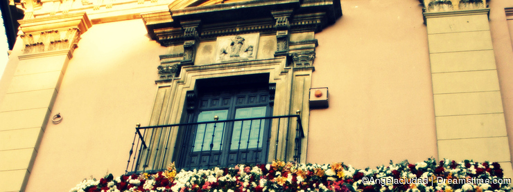 Front of a building with balcony and flowers
