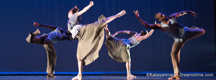 Four dancers in standing leg pose against dark blue background on stage