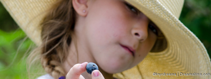 Girl offering a blueberry