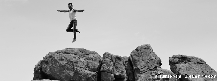 Man jumping or dansing on pile of rocks -B&W-