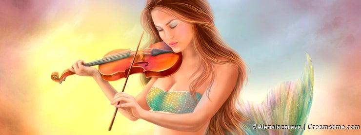 Beautiful woman fantasy mermaid plays on violin on sunset
