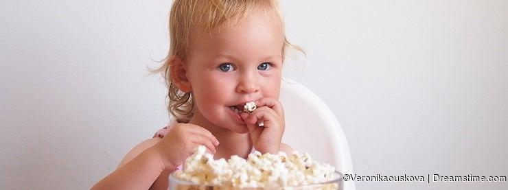 Little blond girl eating popcorn