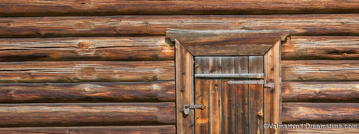 Old log house wood wall with closed door and padlock on it