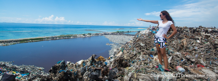 Girl pointing far away standing at the top of trash mountain at garbage dump