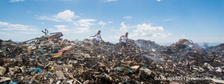 Two girls climbing among mountains of trash
