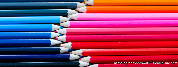 Top View of Collection of Colorful Pencil Crayons Lined Up in Rows Together Meeting at the Tips or Points