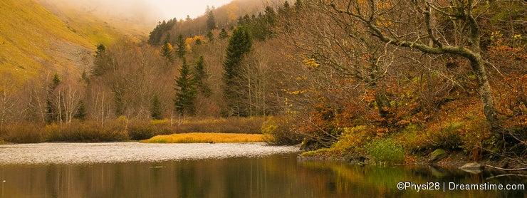High mountain lake in autumn mist