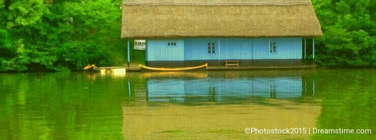 overfiltered blue wooden vintage house on the lake in autumn season