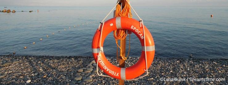 Orange lifebuoy on a pebble beach at the Black Sea