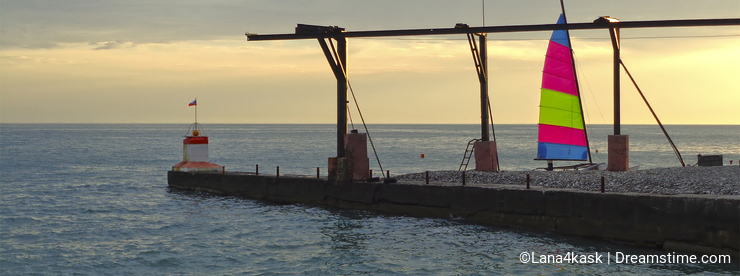 Sailing boat on the sea coast at sunset