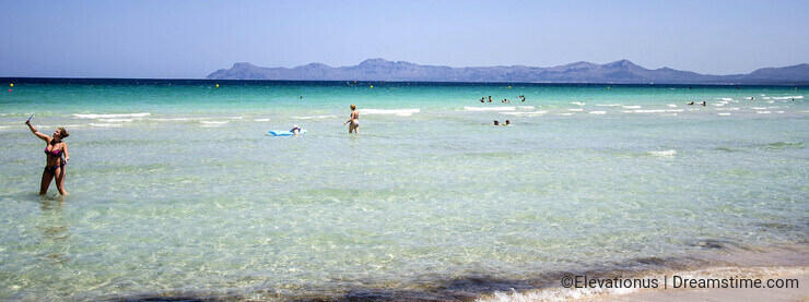 People enjoy a sunny day at Playa del Muro in Mallorca, Spain