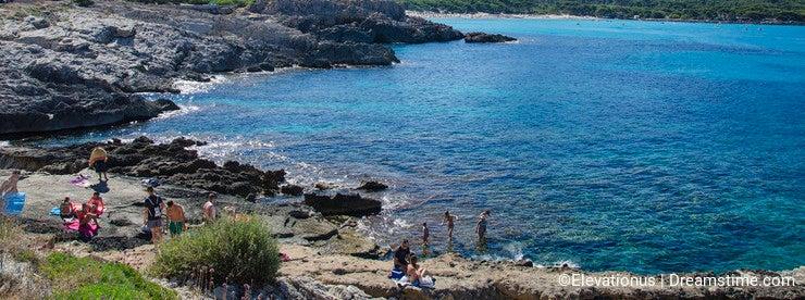 People enjoy a sunny day at Cala Agulla in Mallorca, Spain