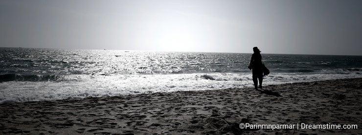 A woman looking at infinite horizon on a bright sunny day at a seashore