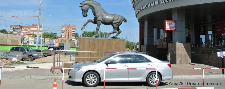 Horse sculpture and car in the city