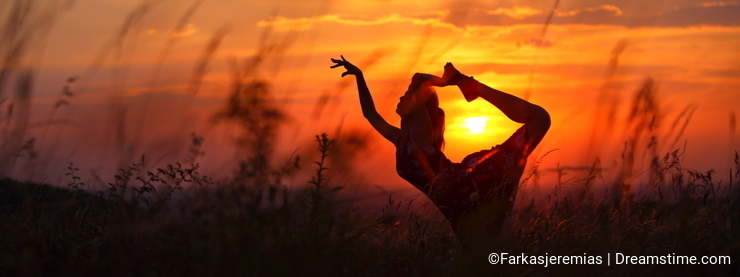 Young woman doing flexible dance move during sunset.