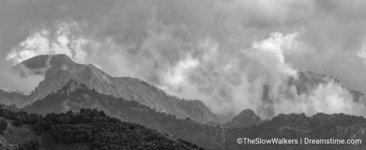 Low clouds roll over and between Spanish mountains.