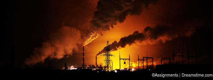 Factories at night, the silhouettes of the pipe producing a noxi