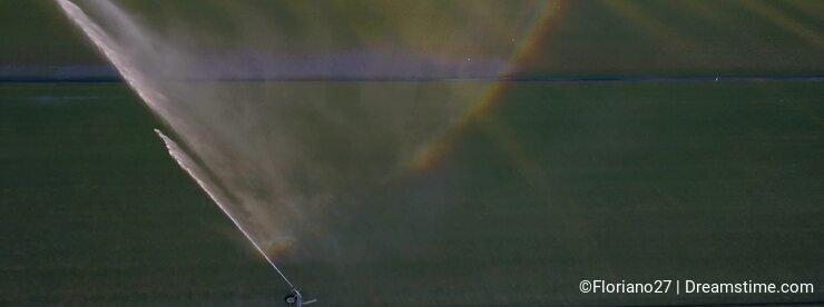 Aerial flight over polo field with large sprinklers watering the grass, forming a rainbow