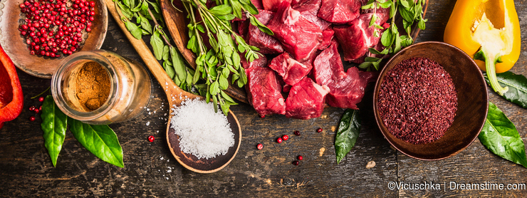 Ingredients for goulash or stew cooking: raw meat, herbs, spices, vegetables and spoon of salt on rustic wooden background, top vi