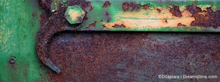 Part of the mechanism for opening the door, painted in a green tint and heavily rusted, spoiled by time