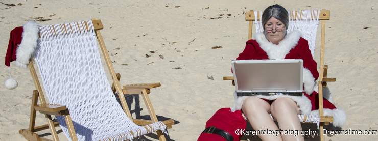 Mrs Claus working on laptop computer on sandy beach