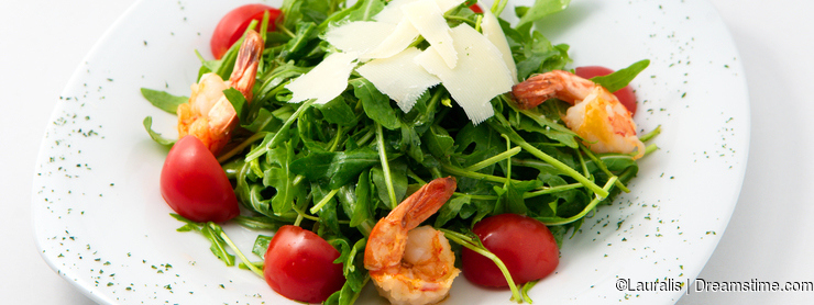 The light salad of arugula cherry tomatoes with shrimp on top decorated with cheese