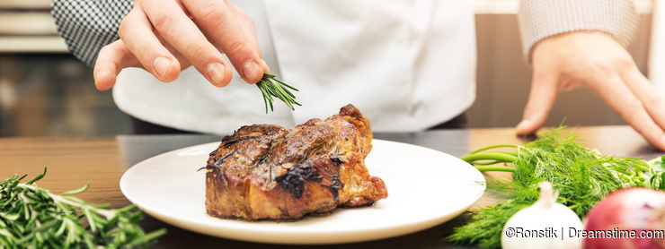 Chef decorating roasted meat with herbs
