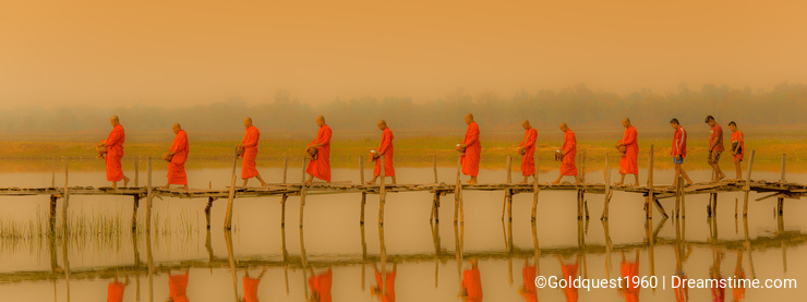 Buddist monks marching to seek alms in morning with fofoggy environment