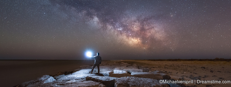 Man watching the Milky Way Galaxy rise from a Jetty