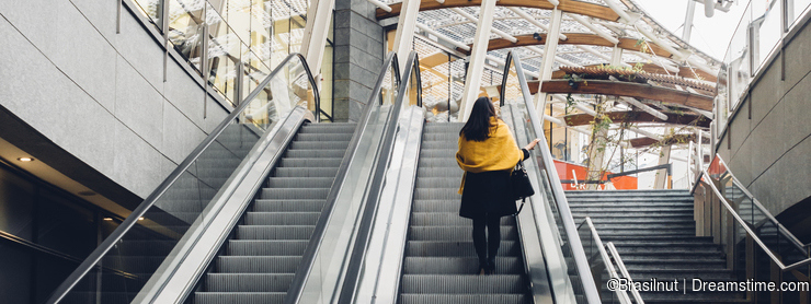 Woman going up escalator in Milan, Italy