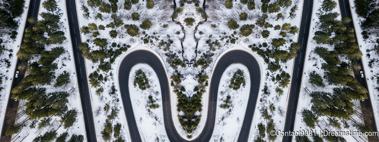 Mirror effect of a winding road mountain pass, in winter time. Aerial view.