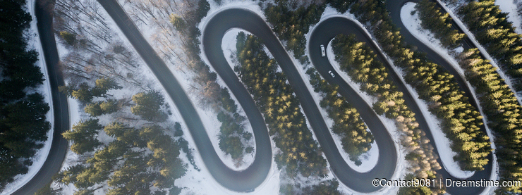 Winding road from high mountain pass, in winter time. Aerial view by drone