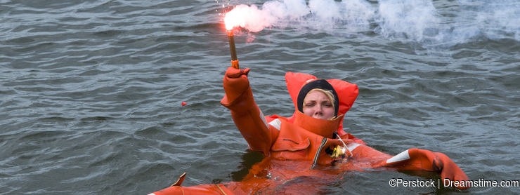 Person floating in survival suit holding red handflare