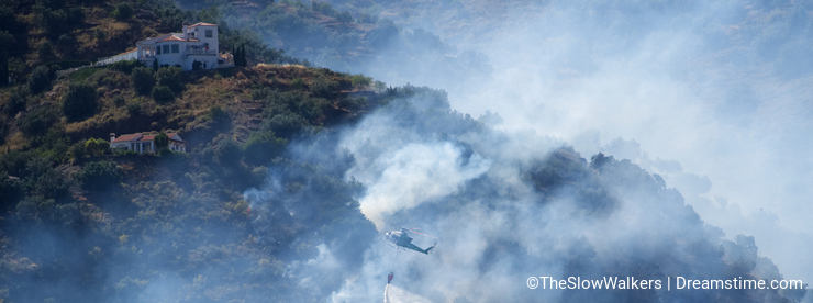 Fire control helicopter Bell 212 drops water onto the burning land below. Between Sayalonga and Arenas, Andalucia, Spain.