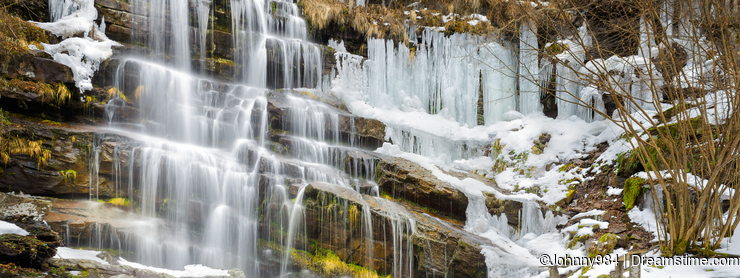 Semi frozen waterfall Tupavica and moss covered rocks
