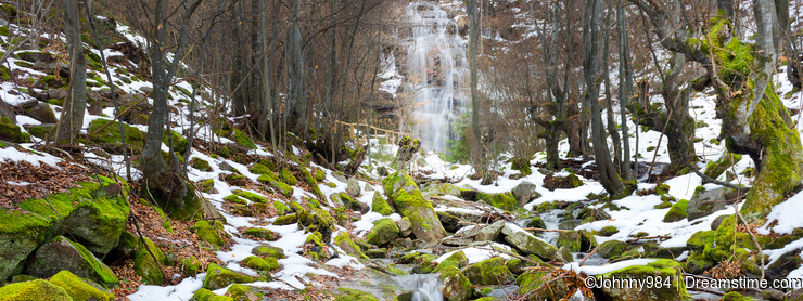Mountain creek, snow and moss covered rocks and iconic waterfall Tupavica